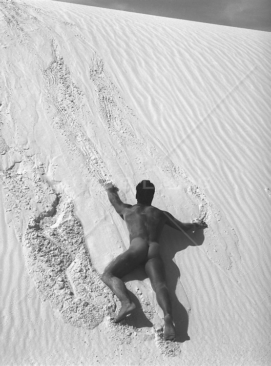 male nude on a large sand dune