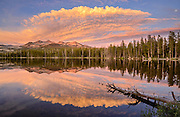 A dramatic sunset reflects across Wrights Lake and the Crystal Range in the Sierra Nevada Mountains West of Lake Tahoe, California