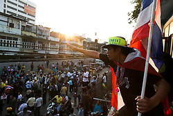 © Licensed to London News Pictures. 17/01/2014. A Anti-Government protestor makes a gesture to the crowd from the roof of the apartment of a suspect who threw an explosive device injuring eight people during an anti-government street rally on January 17, 2014 in Bangkok, Thailand. Anti-government protesters launch 'Bangkok Shutdown', blocking major intersections in the heart of the capital, as part of their bid to oust the government of Prime Minister Yingluck Shinawatra ahead of elections scheduled to take place on February 2. Photo credit : Asanka Brendon Ratnayake/LNP