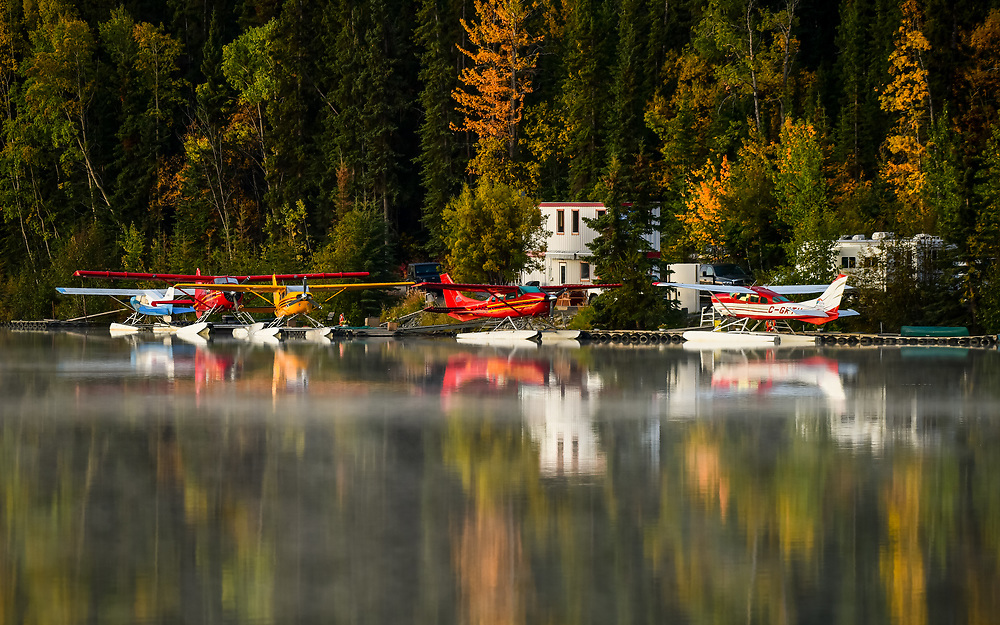 The rising sun shines on Alpine Aviation's base as the morning mist slowly drifts off of Schwatka Lake.