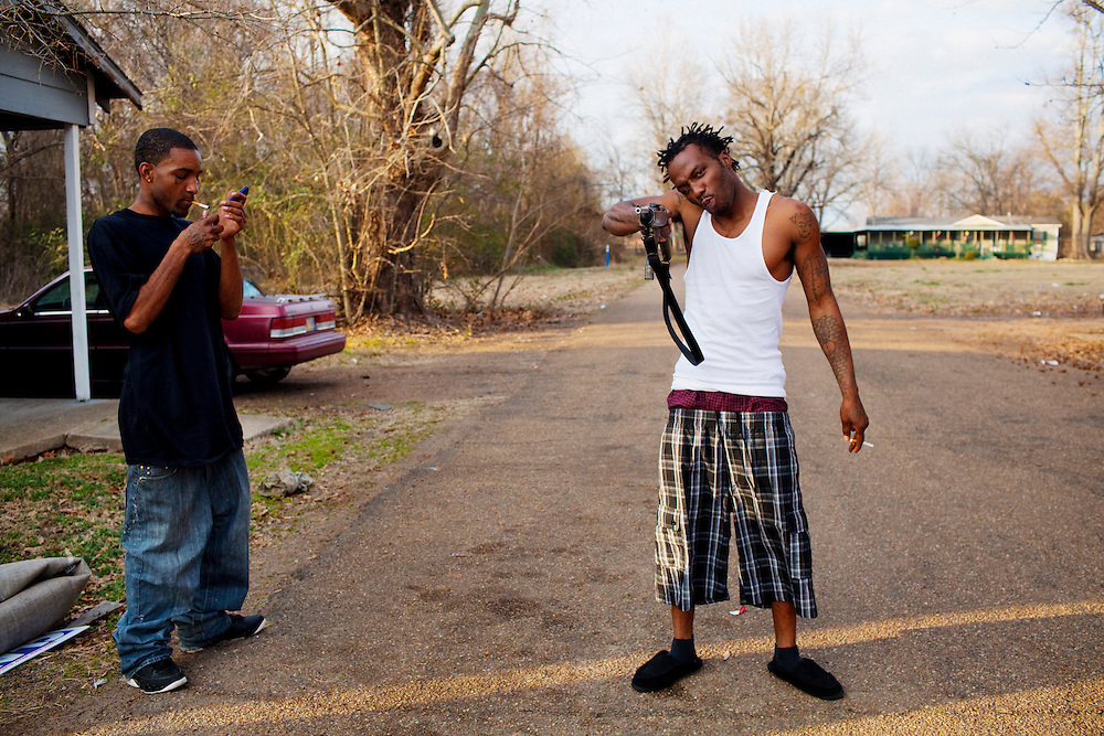 """Roger """"Winky"""" Williams playfully points a gun at the photographer while Lorenzo Foe lights a cigarette in the Baptist Town neighborhood of Greenwood, Mississippi on February 17, 2011."""