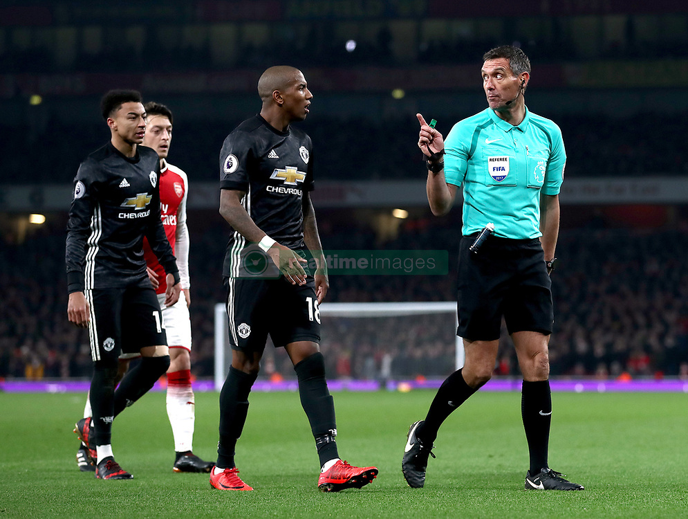 Match referee Andre Marriner (right) speaks with Manchester United's Ashley Young (centre)