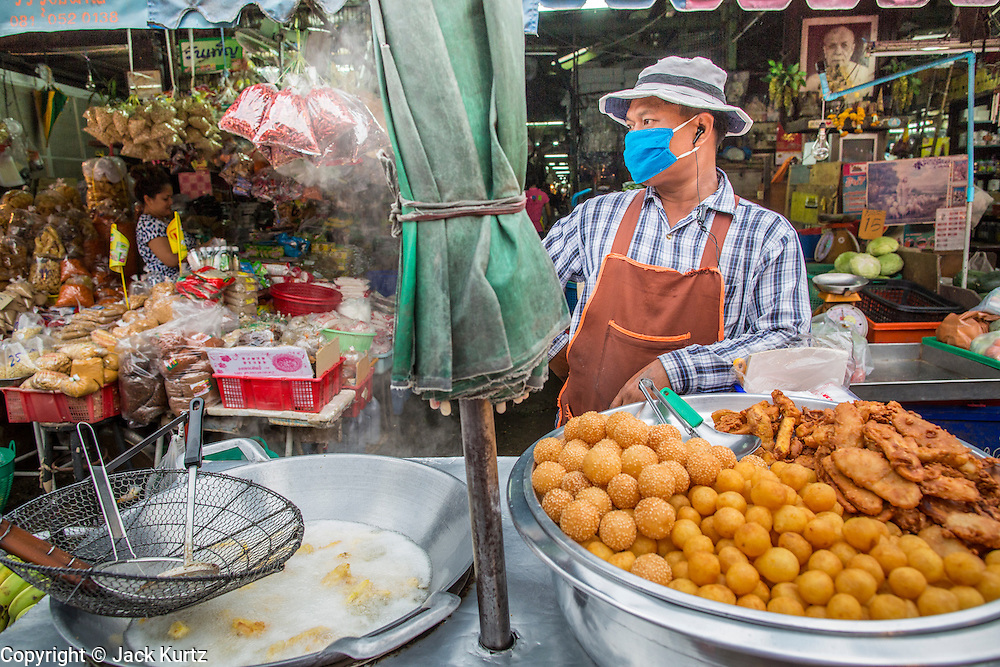 """03 OCTOBER 2012 - BANGKOK, THAILAND:    A fried snack vendor in Khlong Toey Market in Bangkok. Khlong Toey (also called Khlong Toei) Market is one of the largest """"wet markets"""" in Thailand. Thousands of people shop in the sprawling market for fresh fruits and vegetables as well meat, fish and poultry every day.    PHOTO BY JACK KURTZ"""
