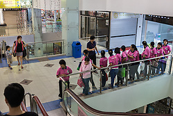 March 22, 2014 - Singapore. Maids are lined up to be taken back to a waiting van who will drive them to their shelter from Bukit Timah shopping centre. © Nicolas Axelrod / Ruom