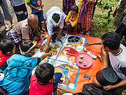 """22 JULY 2016 - TENGANAN DUAH TUKAD, BALI, INDONESIA: People play a game of chance, similar to """"Three Card Monty,"""" before the Pandanus fights in the Tenganan Duah Tukad village on Bali. The ritual Pandanus fights are dedicated to Hindu Lord Indra. Men engage in ritual combat with spiky pandamus leaves and rattan shields. They usually end up leaving bloody scratches on the combatants' backs. The young girls from the community wear their best outfits to watch the fights. The fights have been traced to traditional Balinese beliefs from the 14th century CE. The fights are annual events in the Balinese year, which is 210 days long, or about every seven months in the Gregorian calendar.    PHOTO BY JACK KURTZ"""