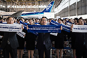 Holdings Inc. President and Chief Executive Officer Shinya Katanozaka and newly hired employees hold up banners for a group photograph during the welcome ceremony of ANA Holdings Inc. at the company's hanger on April 1, 2017 in Tokyo, Japan. Japanese airlines ANA Holdings welcomed 2,800 new employees, the largest number to date for the company. As the majority of Japanese start their career on April 1st after graduating from schools in February or March, it is a custom for large Japanese corporations to hold mass welcoming ceremonies for their new employees. 1/04/2017-Tokyo, JAPAN