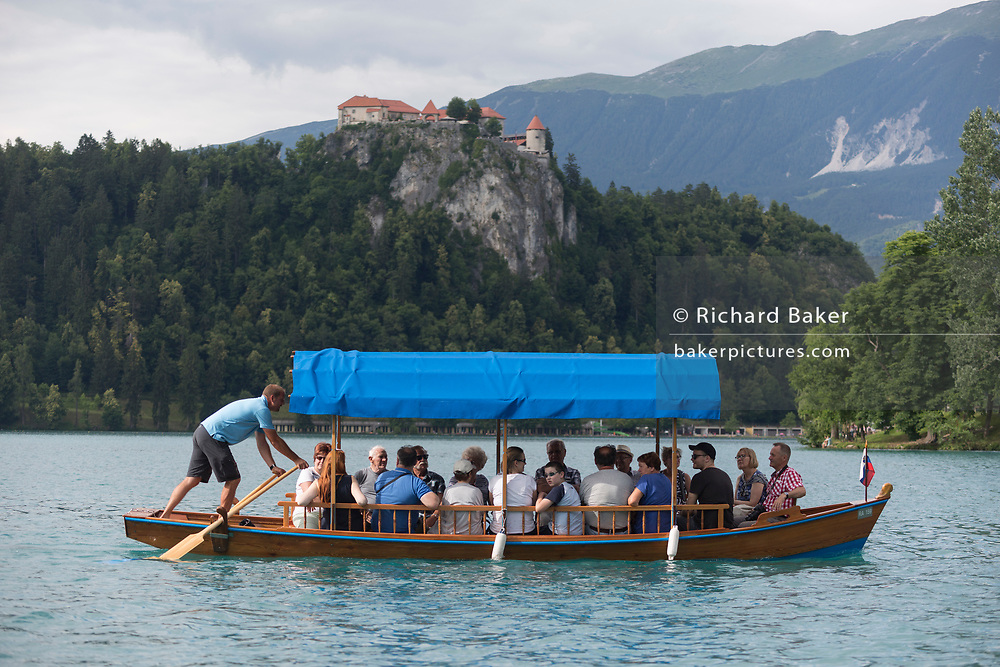 With Bled Castle at the top of cliffs, a tourist boat takes tourists on a tour of Lake Bled, on 18th June 2018, in Bled, Slovenia.