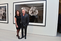 DAVID YARROW and ELIZABETH OFFORD at a private view of photographs by wildlife photographer David Yarrow included in his book 'Encounter' held at The Saatchi Gallery, Duke of York's HQ, King's Road, London on 13th November 2013.