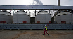 An employee walks past silos containing bio-mass, at the Essent Energie power station, in Geertruidenberg, Netherlands, on Monday March 22, 2010. Bio-mass or compressed wood, is added to the coal for a cleaner burn, in an effort to make the production of electricity more environmentally friendly. Essent Energie is owned by RWE AG. (Photo © Jock Fistick)
