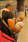 Father meets wife and child at airport after absence.