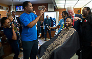 Former President Bill Clinton takes up a pair of scissors and considers making a few cuts on D.J. Anderson's hair while on a visit to Hair Unlimited in the M.L.K. Plaza on Thursday, Nov. 3, 2016.