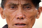 An ex soldier looks at the camera at a market in Sam Neua in Northern Laos.