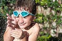 Portrait of very happy kid with splash of water in a backyard