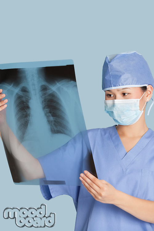 Female surgeon analyzing x-ray report over light blue background