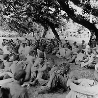 May 1942 - Prisoners rest under the watchful eye of their Japanese captor during the Bataan Death March.
