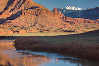 The snowcapped La Sal Mountains with the Colorado River in the foreground, near Moab Utah