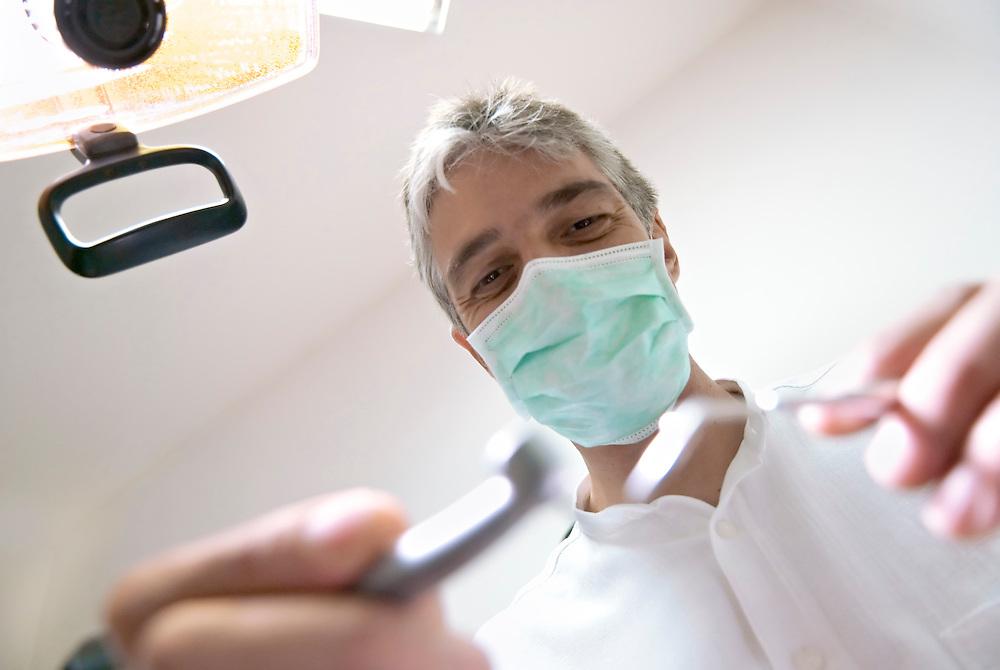 Ein Zahnarzt bei der Behandlung aus der Perspektive des Patienten im Stuhl       | A dentist seen from the perspective of a patient|