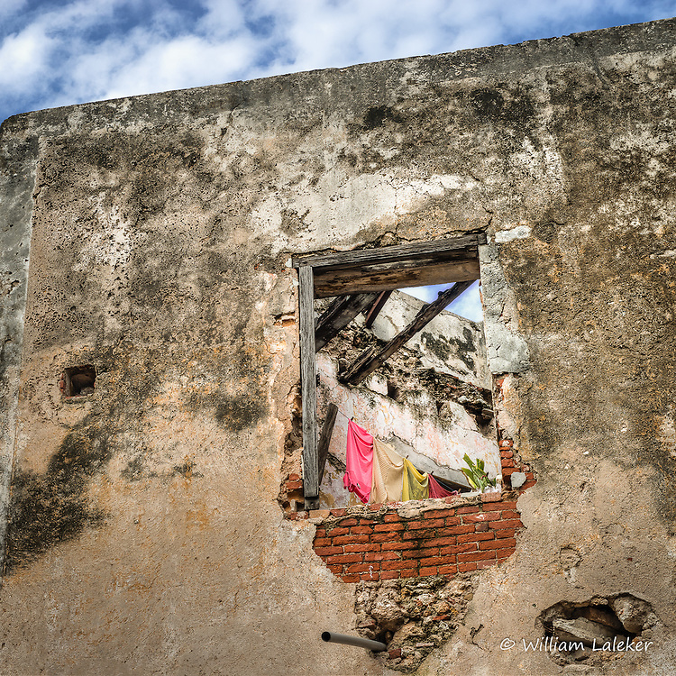 Clothes dry in the fresh air of a roofless building in ruins.  Many of these buildings  are inhabited in Cuba.