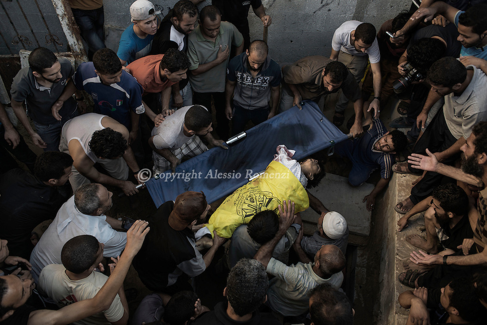 Gaza Strip: Palestinian mourners bury the body of a boy from Bakr family,killed by Israeli naval bombardment in Gaza City, on July 16, 2014. ALESSIO ROMENZI