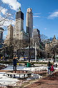 A man stands on a circular wooden bench to avoid the snow, talking on his mobile phone as a woman walks past with a young child in Maddison Square Park, Manhattan, New York City, New York, United States of America.  The iconic Empire State Building and other sky scrapers can be seen in the background. (photo by Andrew Aitchison / In pictures via Getty Images)