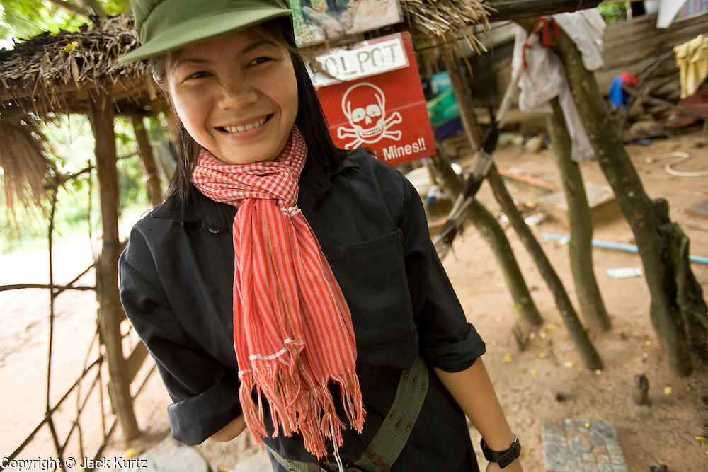 26 JUNE 2006 - SIEM REAP, CAMBODIA: CHUNG SOKNA, 16, wears an old Khmer Rouge type outfit as she greets visitors at the landmine museum operated by Aki Ra in Siem Reap. She lost her arm to a landmine in 1999 while she was looking after her family cows near Siem Reap. Aki Ra was a child soldier drafted by first the Khmer Rouge and later the Vietnamese army. One of his responsibilities was to plant land mines for both sides. After peace came to Cambodia he started his own demining operation. He has been clearing landmines in Cambodia since 1990. Cambodians are still wrestling with the legacy of the war in Vietnam and subsequent civil wars. At one time it was the most heavily mined country in the world and a vast swath of Cambodia, along the Thai-Cambodian border, is still mined. In 2004, more than 800 people were killed by mines and unexploded ordinance still found in the countryside. In addition to demining operations Aki Ra has an orphanage for 20 children maimed by mines.  Photo by Jack Kurtz / ZUMA Press