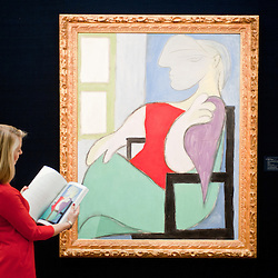 A Sotheby's employee poses in front of a painting entitled 'Femme assise près d'une fenetre', 1932, by Pablo Picasso (Est £ 25-35 million) during the press preview of the Sotheby's forthcoming February sales of Impressionist & Modern Art and Contemporary Art in London, including works by Picasso, Bacon, Monet, Richter, Miró, Basquiat.