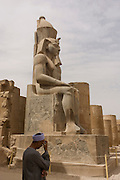 A local guide and caretaker beneath the massive stitting colossus in the Court of Ramesses II at the ancient Egyptian Luxor Temple, Nile Valley, Egypt. The temple was built by Amenhotep III, completed by Tutankhamun then added to by Rameses II. Towards the rear is a granite shrine dedicated to Alexander the Great  and in another part, was a Roman encampment. The temple has been in almost continuous use as a place of worship right up to the present day.