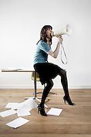 Woman sitting on desk shouting through megaphone