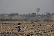 A young Egyptian girl looks towards a hot air balloon on wasteground in a West Bank village of the modern city of Luxor, Nile Valley, Egypt.
