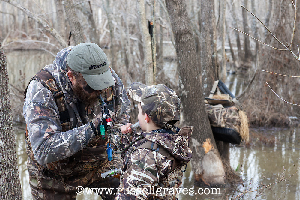 HUNTER SHOWING A BOY HOW TO BLOW A DUCK CALL
