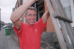 Portrait of builder holding roof support smiling,