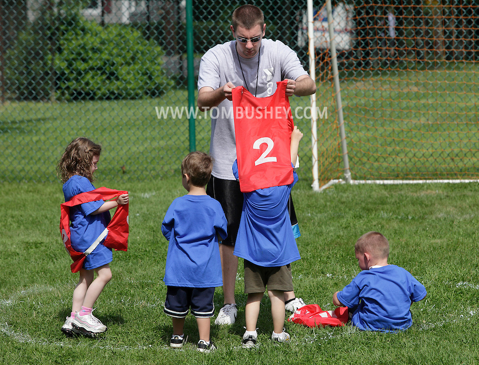 Middletown, New York - A coach helps a boy take off his numbered vest at the end of a youth soccer program at the Middletown YMCA on May 28, 2011.