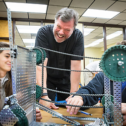 Lisa Johnston | lisajohnston@archstl.org  | Twitter: @aeternusphoto  Father Kevin Schmittgens is the president and Chaplain at St. Francis Borgia Regional High School in Washington.  He laughed with students in a Principals of Engineering class who were building a simple machine. On the left is Erica Huber and with his face blocked by a gear is Parker Durbin.  They are both seniors.