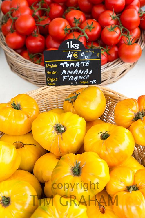 Vine tomatoes among salad vegetables and fresh food on sale at street market Bordeaux, France