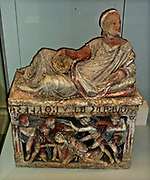 Painted cinerary urn with a reclining figure of a man set above a moulded battle relief. Etruscan, circa 150-100 BC, from Chiusi, Italy