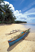 Outrigger canoe on palm tree-lined beach, village of Walung, Kosrae, Micronesia.  .