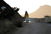 A U.S. Border Patrol agent drives on a dirt road along the U.S./Mexico border wall near the San Pedro River, Cochise County, Hereford, Arizona, USA.