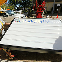 Josh Easley, of Tupelo and a employee at Duncan Signs, and Lee Duncan, owner of Duncan signs, move a new LED box sing off of their truck to prep it for installation at The Church of the Living God in Tupelo on Wednesday morning.