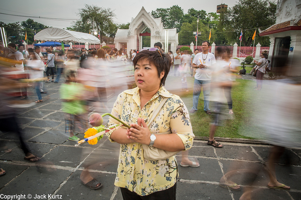 "25 FEBRUARY 2013 - BANGKOK, THAILAND:  Thais pray in front of Wat Benchamabophit Dusitvanaram (popularly known as either Wat Bencha or the Marble Temple) while people behind them participate in a procession on Makha Bucha Day. Thais visit temples throughout the Kingdom on Makha Bucha Day to make merit and participate in candle light processions around the temples. Makha Bucha is a Buddhist holiday celebrated in Myanmar (Burma), Thailand, Cambodia and Laos on the full moon day of the third lunar month (February 25 in 2013). The third lunar month is known in Thai is Makha. Bucha is a Thai word meaning ""to venerate"" or ""to honor"". Makha Bucha Day is for the veneration of Buddha and his teachings on the full moon day of the third lunar month. Makha Bucha Day marks the day that 1,250 Arahata spontaneously came to see the Buddha. The Buddha in turn laid down the principles his teachings. In Thailand, this teaching has been dubbed the 'Heart of Buddhism'.     PHOTO BY JACK KURTZ"