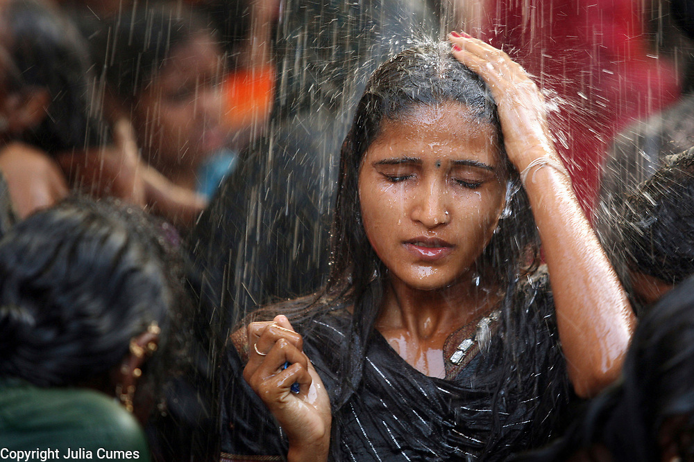 "A young woman bathes in a communal bathing area before worshipping at the Yellamma temple during the Yellamma Jatre (fesival) in Saundatti, India. As part of Yellamma custom, all worshippers must wash before worshipping and during the full moon festical, young girls from impoverished lower caste families are ""married"" to the goddess Yellamma to appease her.  Once they are married to Yellamma, they are regarded as servants to the goddess and must perform temple duties as well as satisfy the sexual needs of the priests and other men.  They may no longer marry a mortal and often end up being sold by unscrupulous priests to pimps who take them to work in the red-light districts of India's urban areas."