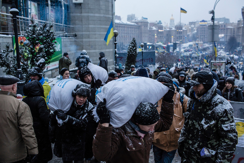 KIEV, UKRAINE - DECEMBER 11: Anti-government protesters carry bags of snow to be used to reinforce a barricade blocking street access to Independence Square, known as the Euromaidan, on December 11, 2013 in Kiev, Ukraine. Thousands of people have been protesting against the government since a decision by Ukrainian president Viktor Yanukovych to suspend a trade and partnership agreement with the European Union in favor of incentives from Russia. (Photo by Brendan Hoffman/Getty Images) *** Local Caption ***