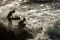 Spearfishers enter the water from a rocky outcrop, Western Cape, South Africa
