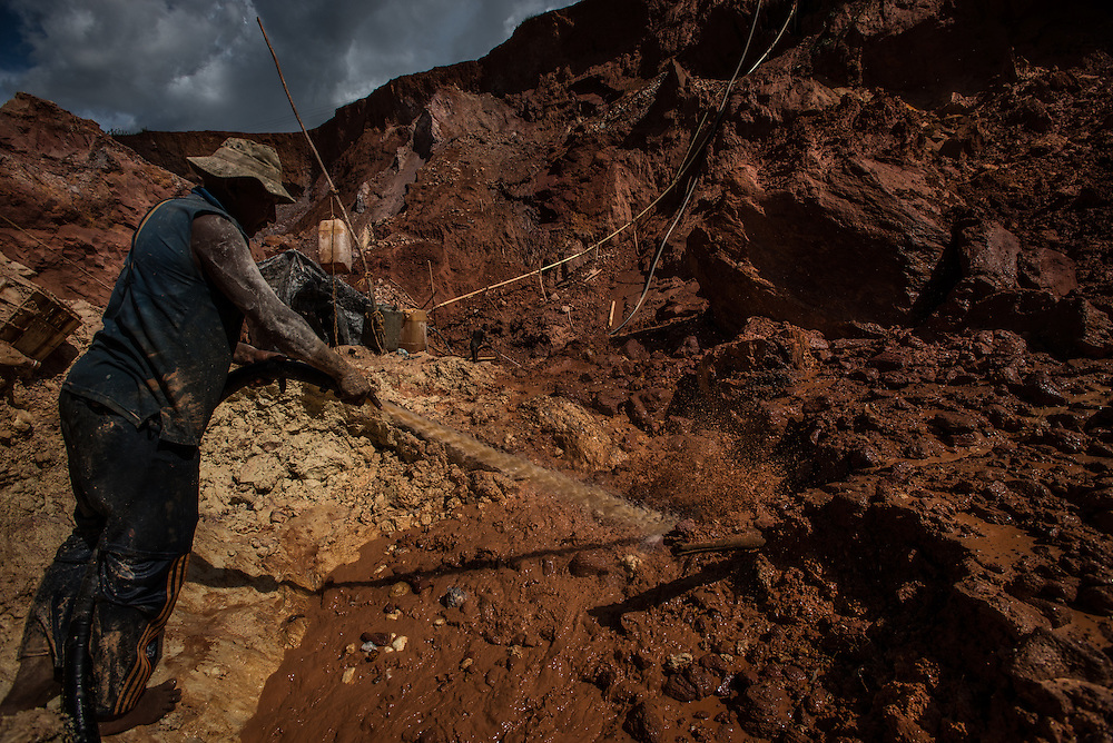 """LAS CLARITAS, VENEZUELA - JULY 20, 2016:  Carlos Raphael, 50, (left) and his crew illegally mine for gold at the """"Cuatro Muertos"""" (""""Four Dead"""") mine, named so because four miners have died here since the mine was dug.  Raphael has contracted malaria ten times, and said everyone in his crew has also had it multiple times.  Thousands of Venezuelans are flocking to illegal gold mines, like this one, in hopes of surviving the current economic crisis by earning in gold instead of the national currency, whose value steadily falls due to the world's highest inflation.  From this remote part of the jungle the migrant miners have become the vectors of a new epidemic of malaria, because the hot, swampy conditions of the mines make for an ideal breeding ground for mosquitos. Miners spread the disease as they return home with earnings or pay visits to family members. The economic crisis has also left the government without the financial resources to control the disease - they are unable to fumigate homes, provide medicines to everyone that is sick, or even to test all patients with symptoms of malaria in many places. PHOTO: Meridith Kohut"""