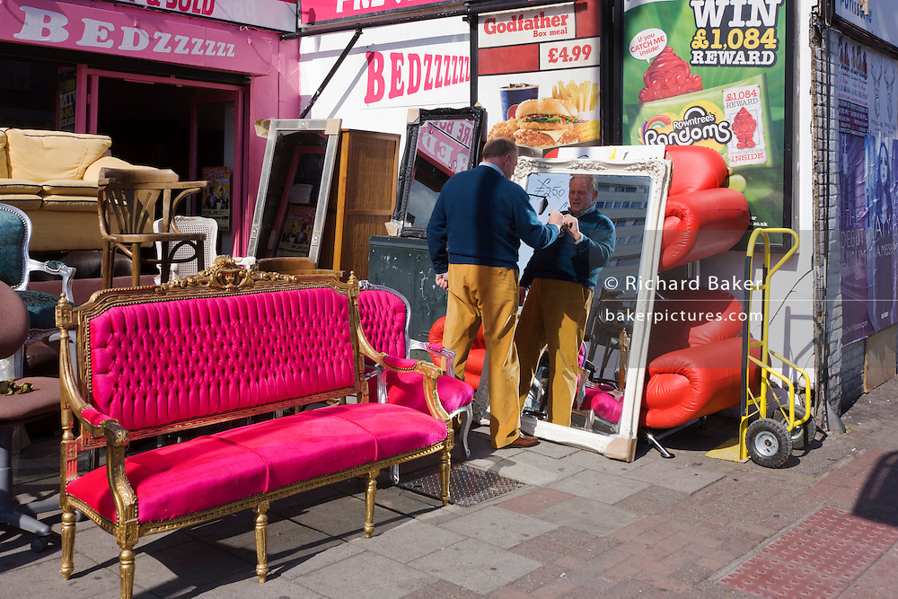 Shop owner writes a reduced price on an upright mirror with bright furniture on sale in a London street.