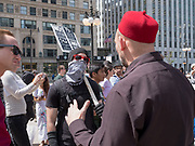 An anti-Trump protester with his face covered and another protester have a discussion.