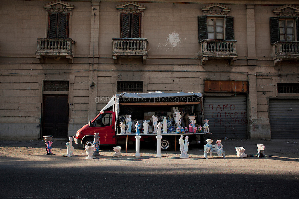 Rosarno, Italy - 31 August, 2012: A truck selling religious and pagan plaster statues is here on the main street of Rosano, Italy, a mafia stronghold on August 31, 2012. <br /> <br /> Rosarno is an agricultural area best known for the violent race riots that erupted here in January 2010. and for being a hotbed of the 'Ndrangheta, a Mafia-type criminal organisation based in Calabria. The local 'Ndrangheta dominates the fruit and vegetable businesses in the area, according to Francesco Forgione, a former head of Italy's parliamentary Antimafia Commission. In December 2008, the entire town council was dissolved on orders from the central government and replaced by a prefectoral commissioner because it had been infiltrated by 'Ndrangheta members and their known associates.<br /> <br /> Calabria is one of the poorest Italian regions which suffers from lack of basic services (hospitals without proper equipment, irregular electricity and water), the product of disparate political interests vying for power. The region is dominated by the 'Ndrangheta (pronounced en-Drang-get-A), which authorities say is the most powerful in Italy because it is the welthiest and best organized.<br /> <br /> The region today has nearly 20 percent unemployment, 40 percent youth unemployment and among the lowest female unemployment and broadband Internet levels in Italy. Business suffer since poor infrastructure drives up transport costs.<br /> <br /> Last summer the European Union's anti-fraud office demanded that Italy redirect 380 million euros in structural funding away from the A3 Salerno - Reggio Calabria highway after finding widespread evidence of corruption in the bidding processes.
