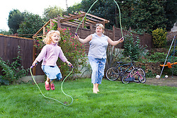 Mother and daughter skipping in the garden,