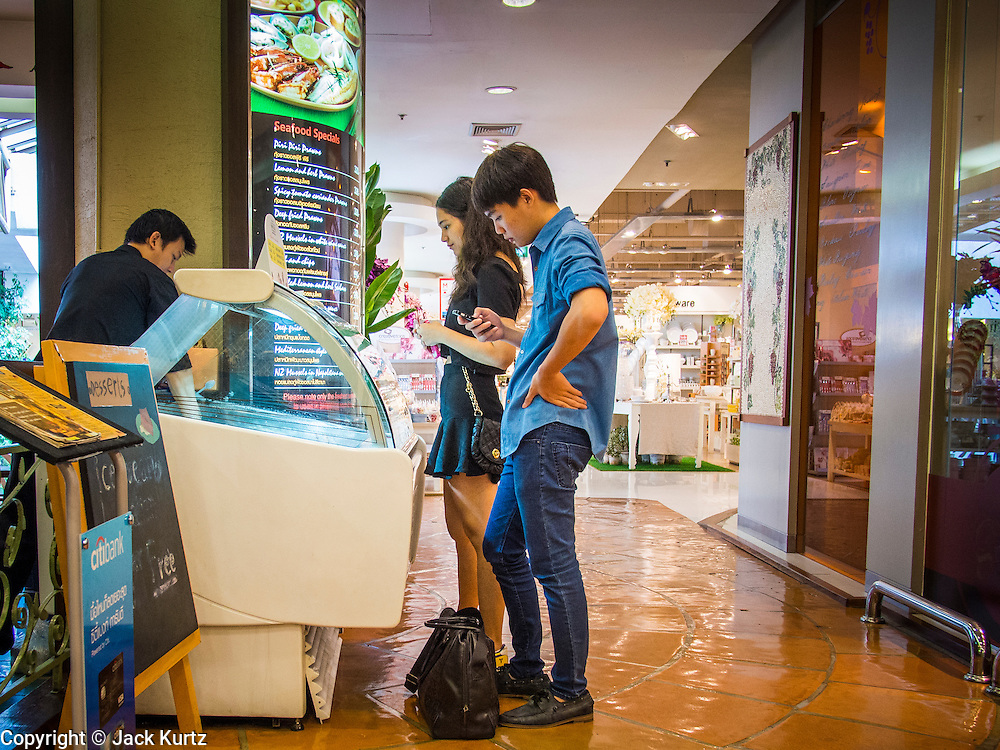 """24 AUGUST 2013 - BANGKOK, THAILAND: Thais buy imported gelato in a nearly empty shopping mall in Bangkok. Thailand entered a """"technical"""" recession this month after the economy shrank by 0.3% in the second quarter of the year. The 0.3% contraction in gross domestic product between April and June followed a previous fall of 1.7% during the first quarter of 2013. The contraction is being blamed on a drop in demand for exports, a drop in domestic demand and a loss of consumer confidence. At the same time, the value of the Thai Baht against the US Dollar has dropped significantly, from a high of about 28Baht to $1 in April to 32THB to 1USD in August.     PHOTO BY JACK KURTZ"""