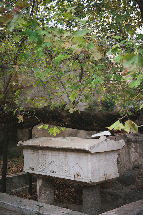 An ancient sarcophagus turned into a water fountain during the Ottoman period, under a plane tree inside the castle of Chios.