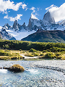 "Mount Fitz Roy (3405 meters or 11,170 feet) rises abruptly above native forest in the southern Andes mountains, near El Chaltén village, in Los Glaciares National Park, Argentina, South America. In 1877, explorer Perito Moreno named ""Cerro Fitz Roy"" for Robert FitzRoy (no space before the capital R) who, as captain of the HMS Beagle, had travelled up the Santa Cruz River in 1834 and charted much of the Patagonian coast. First climbed in 1952 by French alpinists Lionel Terray and Guido Magnone, Mount Fitz Roy has very fickle weather and is one of the world's most challenging technical ascents. It is also called Cerro Chaltén, Cerro Fitz Roy, and Monte Fitz Roy (with a space before the R). Chaltén comes from a Tehuelche (Aonikenk) word meaning ""smoking mountain"" (explained by frequent orographic clouds). Cerro is a Spanish word meaning hill. El Chaltén village was built in 1985 by Argentina to help secure the disputed border with Chile, and now tourism supports it, 220 km north of the larger town of El Calafate. The foot of South America is known as Patagonia, a name derived from coastal giants, Patagão or Patagoni, who were reported by Magellan's 1520s voyage circumnavigating the world and were actually Tehuelche native people who averaged 25 cm (or 10 inches) taller than the Spaniards. Mount Fitz Roy is the basis for the Patagonia company's clothing logo, after Yvon Chouinard's ascent and subsequent film in 1968."